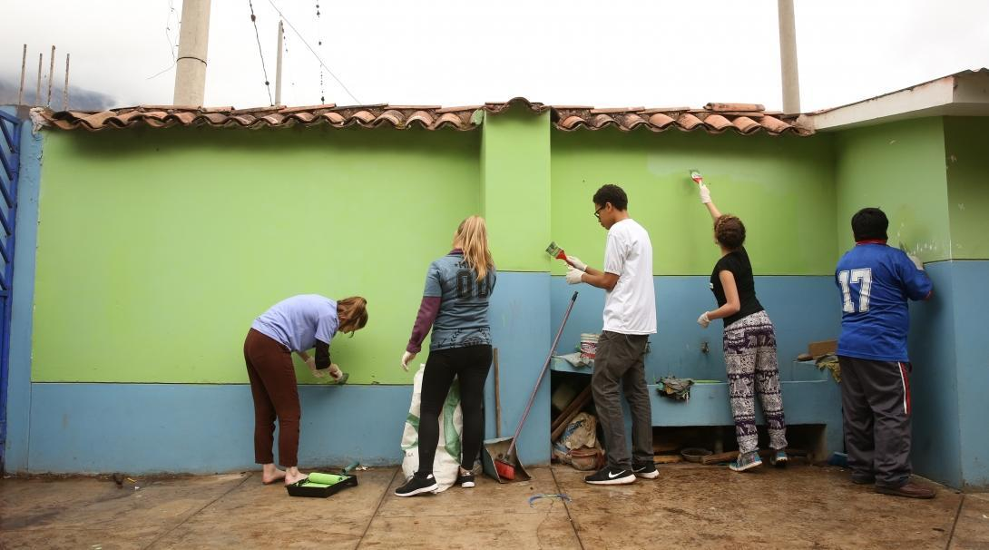 A group of Projects Abroad volunteers working with children in Peru paint a school to help enhance the learning environment.